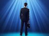 businessman standing in beam of light