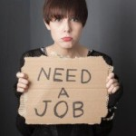 "woman holding sign reading ""need a job"""