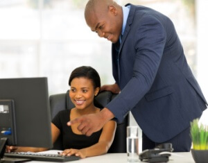 boss guiding his employee with her work
