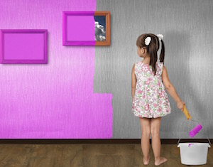 little girl painting wall pink