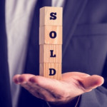 Businessman holding a sold sign