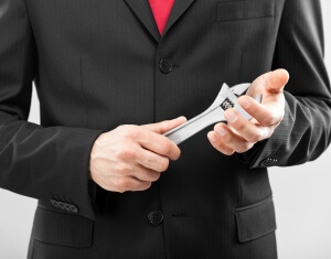 Businessman holding an adjustable wrench
