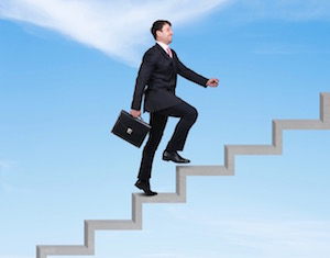 businessman walking up stairs into sky