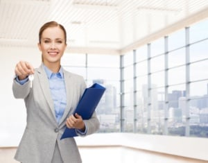smiling businesswoman with folder and keys