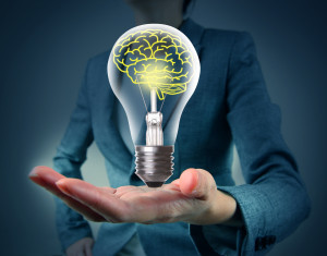 Light bulb in hand with brain