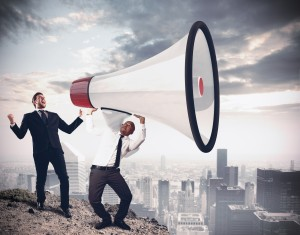Businessman shouting into giant megaphone over the city