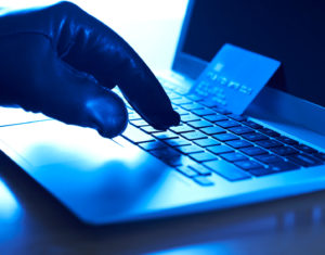 4 tips to prevent e commerce credit card processing fraud cyber criminal with stolen credit card and laptop colourmoves