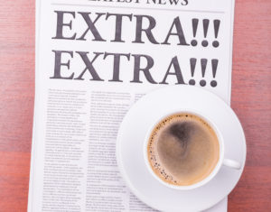 newspaper with the headline EXTRA! EXTRA! and coffee