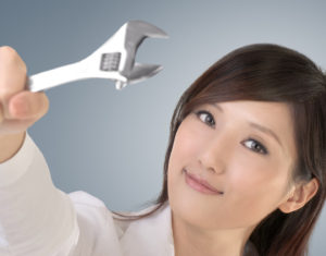 Business woman fix by using wrench