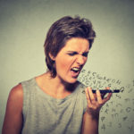Portrait angry young woman screaming on mobile phone