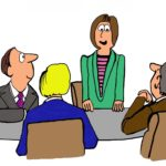 businesswoman standing and speaking in a meeting.