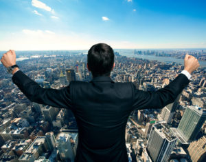 Businessman raising his arms in front of a big city