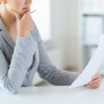 close up of woman reading papers