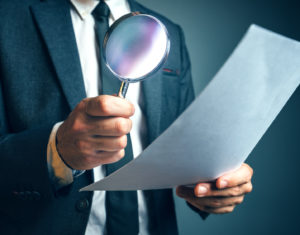 Reading Legal Contract Agreement With Magnifying Glass