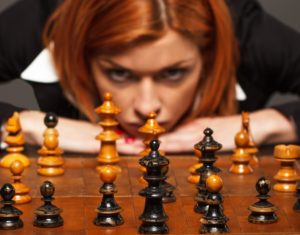 Businesswoman thinking about her next move in a game of chess
