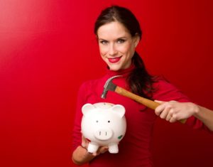 Woman Breaking Piggy Bank with Hammer