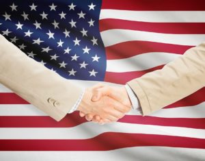 Businessmen handshake with United States flag on background