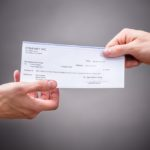 Businessperson Giving Cheque To Colleague