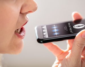 Woman Using Voice Recognition Function On Mobile Phone