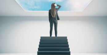businesswoman looking through glass ceiling
