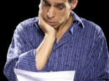 stressed out man reading unpaid bills