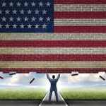 businessman lifting wall painted as U.S. flag