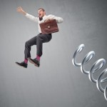 businessman bouncing off spring