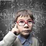 young boy in front of mathmatical formulas on blackboard