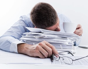 exhausted man on pile of papers